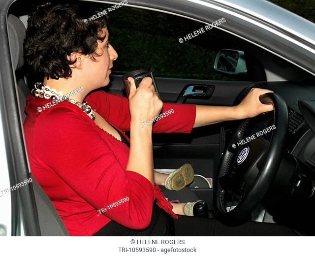 Woman using a drinking cup in her car