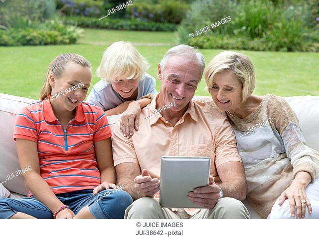 Grandparents and grandkids using digital tablet on outdoor sofa