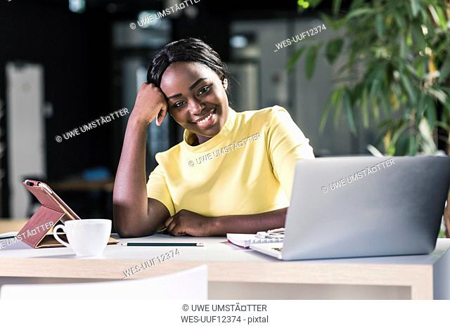 Smiling businesswoman with laptop and tablet