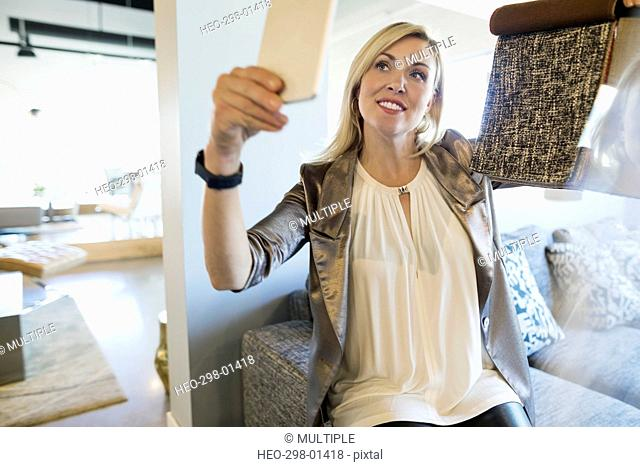 Interior designer holding fabric swatch video chatting with digital tablet in home furnishings store