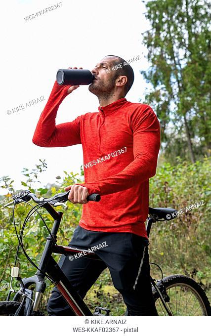 Athlete mountainbiking in nature, taking a break, drinking water