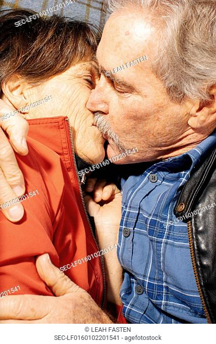 Close-up of senior couple lying down on blanket and kissing in park