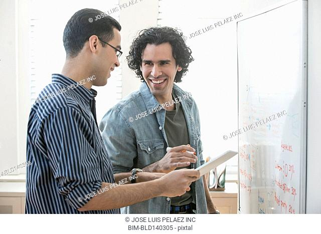 Businessmen with digital tablet writing on whiteboards in office