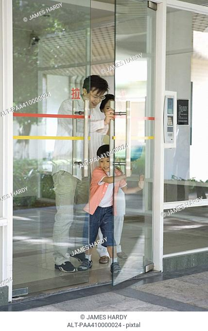 Family coming through door