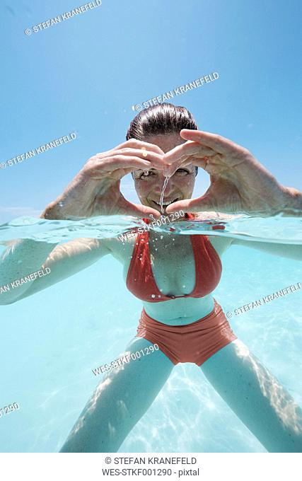 Maldives, woman shaping a heart with her hands in shallow water