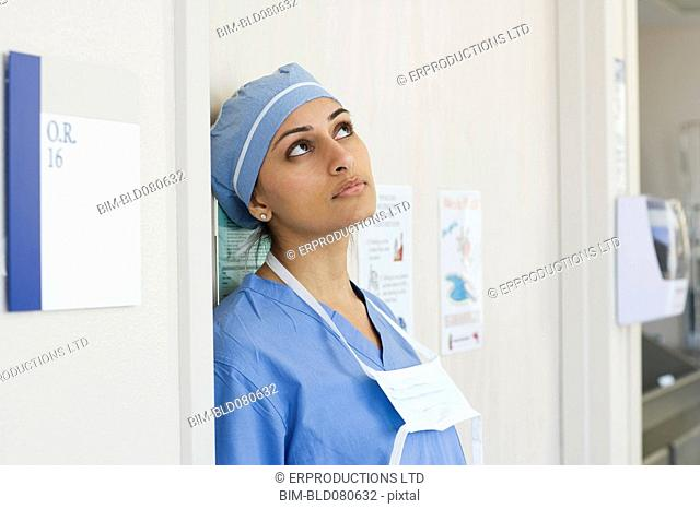 Tired Asian surgeon leaning against wall