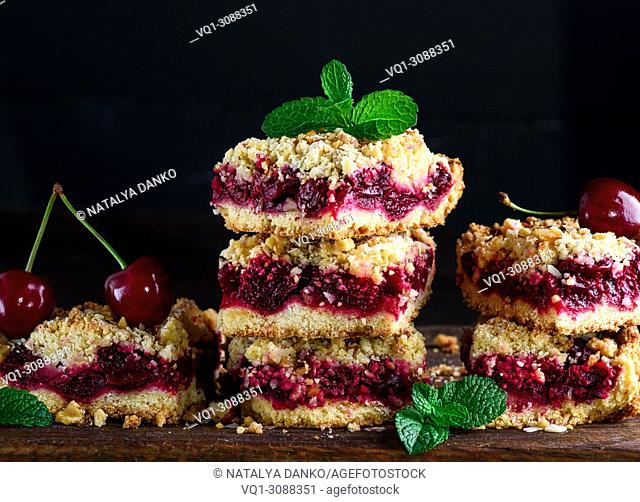 stack of square slices of a pie with a cherry, a black background