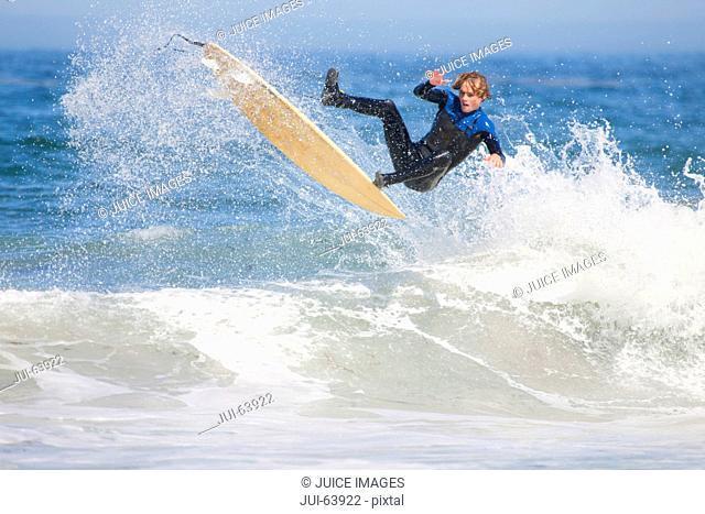 Surfer, mid air, falling off surfboard