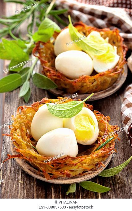 Boiled quail eggs in baked nests of potatoes. With sage and rosemary