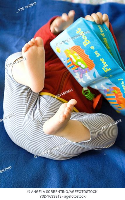 Toddler baby playing with book