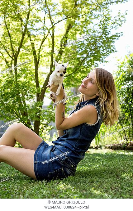 Happy woman sitting on meadow in the garden with her Chihuahua