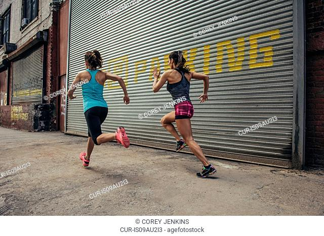 Two female runners running in city street