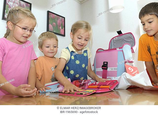 Girl, 6 years, has got new schoolbag and pencil case, other children are watching