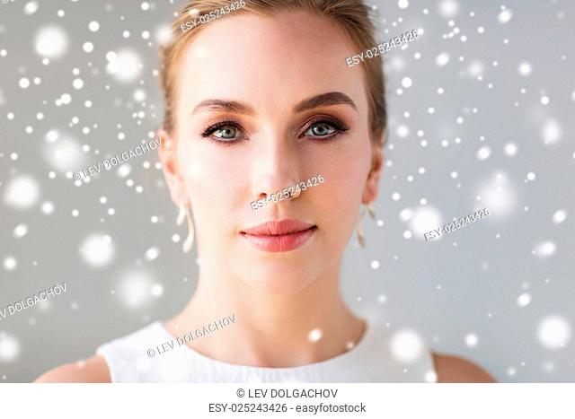 christmas, holidays, beauty, wedding and people concept - close up of beautiful woman or bride in white dress over gray background and snow