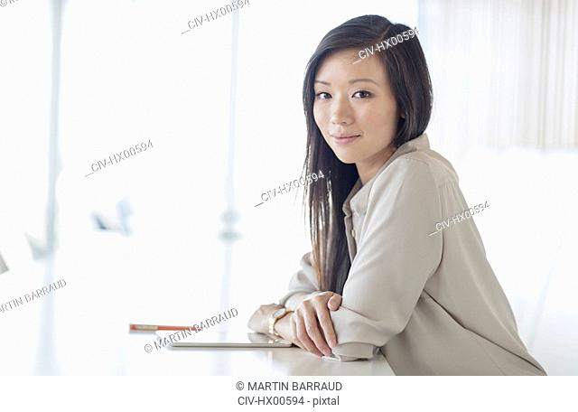 Portrait smiling businesswoman with digital tablet in conference room