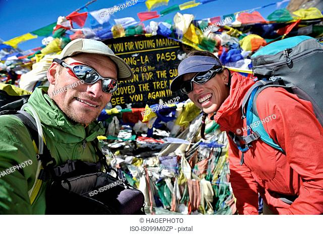 Trekkers looking at camera near prayer flags, Thorung La, Nepal