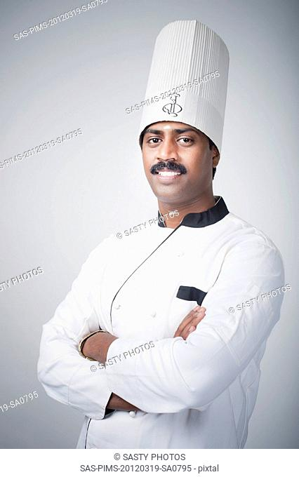 South Indian chef standing with his arms crossed and smiling