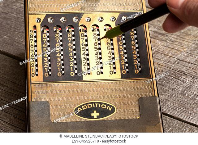 Vintage manual calculator from 1930s with a stylus