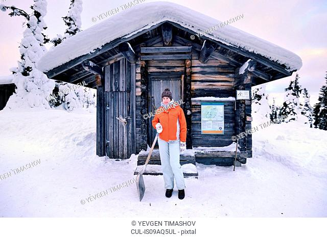 Portrait of young woman with snow shovel outside log cabin, Posio, Lapland, Finland