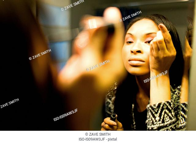 Over shoulder mirror image of young woman putting on eye shadow in bathroom