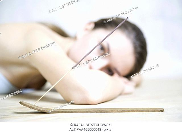 Woman lying on stomach, head resting on arms, looking at camera, incense in foreground