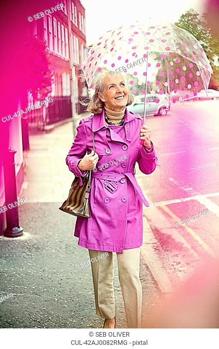 Older woman carrying colorful umbrella