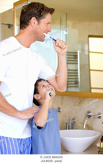 Father and son 6-8 brushing their teeth in bathroom, smiling