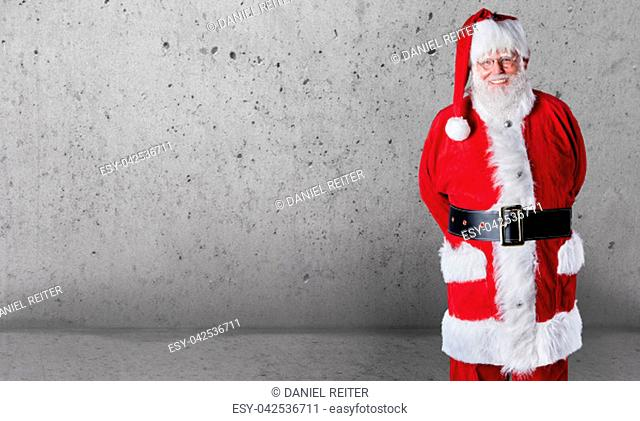 Happy jovial Santa Claus with copy space over a grey textured wall background to wish you a Merry Christmas