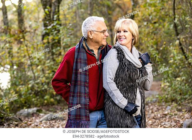 A happy 65 year old man and a 59 year old blond woman hugging in a forest setting