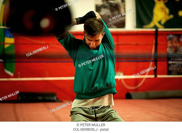 Young man exercising in boxing gym, stretching