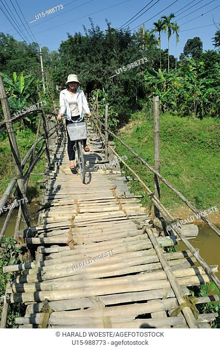 Asia, Vietnam, Hue  Vietnamese woman on bicycle crossing a toll-bridge  Designated a UNESCO World Heritage Site in 1993, Hue is honoured for its complex of...