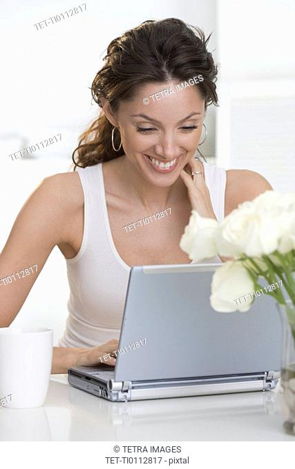 Smiling woman with laptop and cup