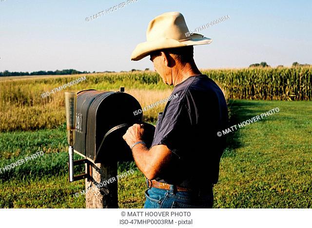 Farmer checking mail box in rural field