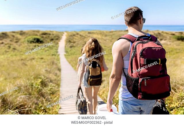 Back view of friends on the way to the beach