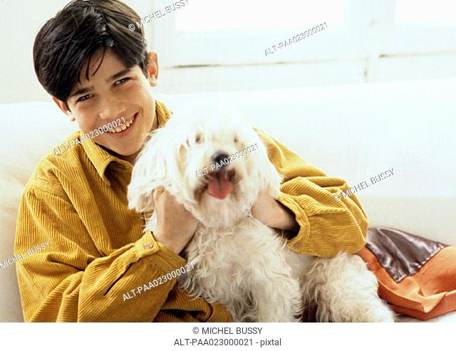 Young man posing with a dog on couch, portrait
