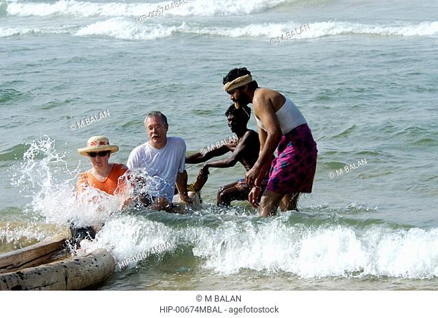 TOURISTS AND LOCAL FISHERMEN ON CATAMRAN AT CHOWARA BEACH NEAR KOVALAM