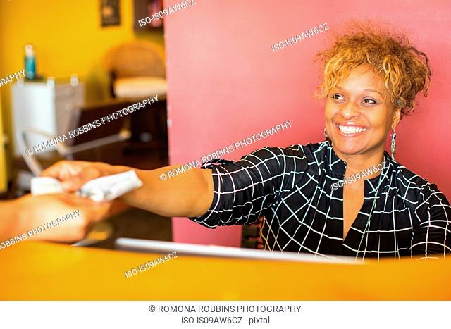 Salon worker handing change to customer