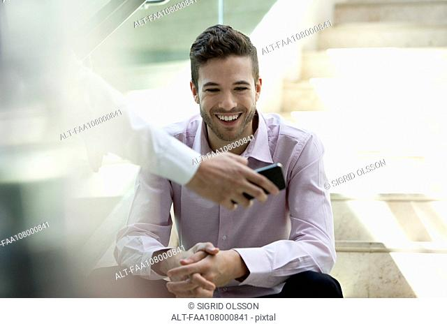 Businessman showing colleague content on smartphone