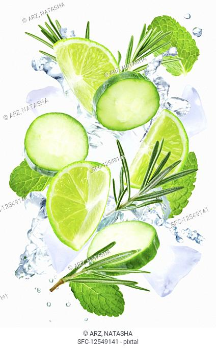 Lime, cucumber, rosemary and mint flying with ices and water splash