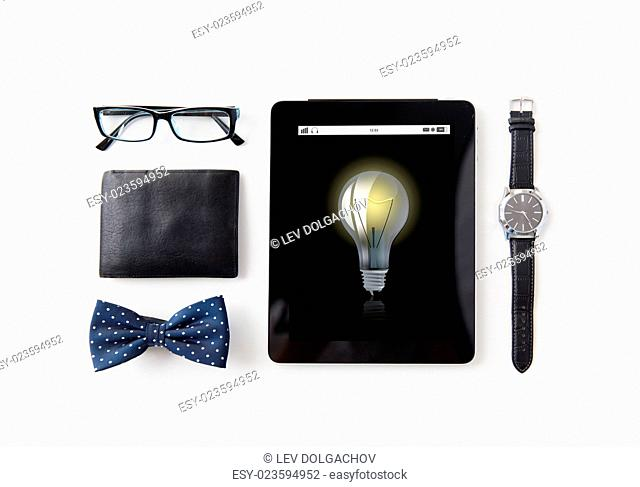 technology and objects concept - tablet pc computer with light bulb icon, wallet, eyeglasses, bowtie and wristwatch on table