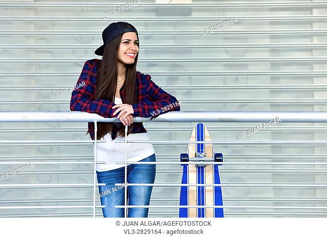 Shot of smiling female in cap standing near skate while posing for camera looking away