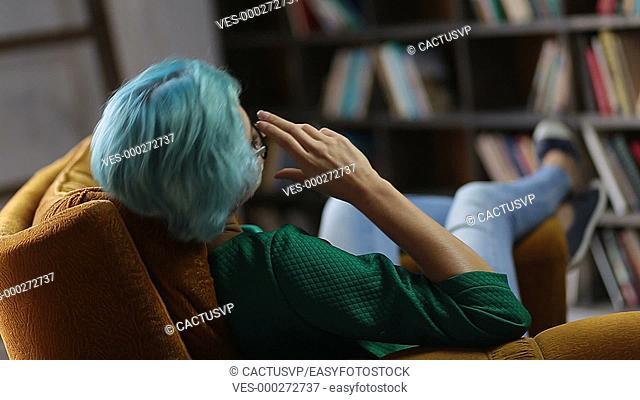 Pondering trendy woman relaxing in cozy chair