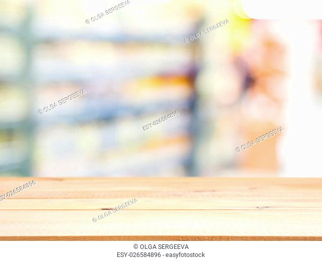 Wooden board empty table in front of blurred background. Perspective light wood over blur in supermarket - can be used for display or montage your products
