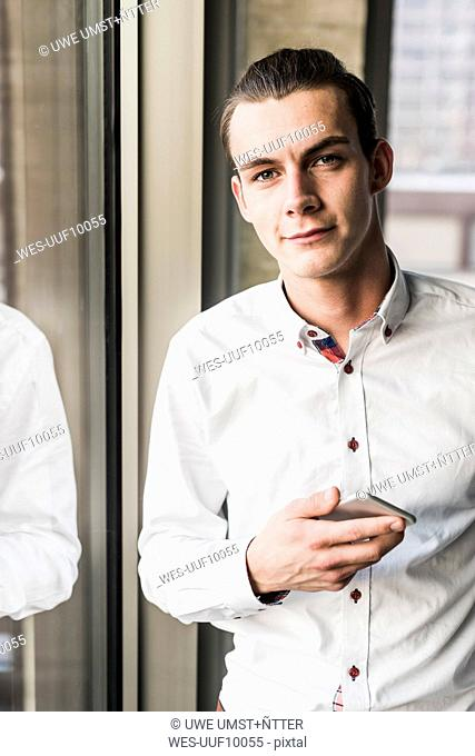 Portrait of young businessman holding cell phone