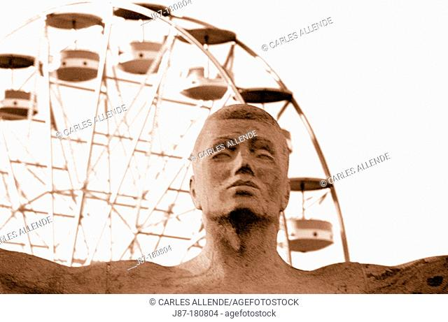 Head of dancer of the Sardana Monument and big wheel in background. Barcelona. Spain