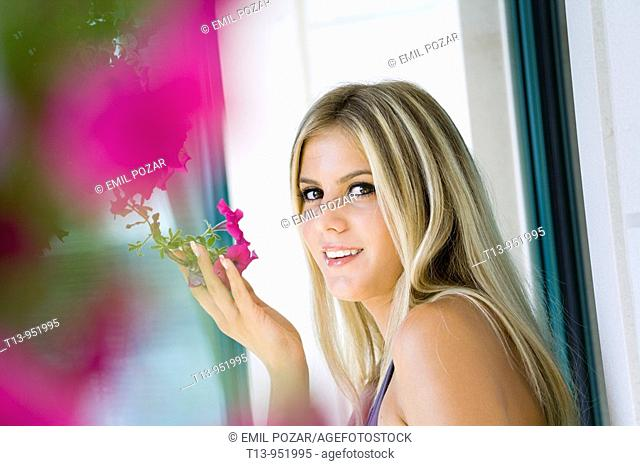 Attractive young woman is smelling a flower