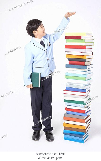 Elementary school boy in school uniforms holding a book and gesturing measuring the height of a pile of books