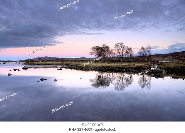 Evening view over flat calm Loch Ba with pink afterglow in sky, reflected in loch and snow-capped mountains in distance, Rannoch Moor, near Fort William