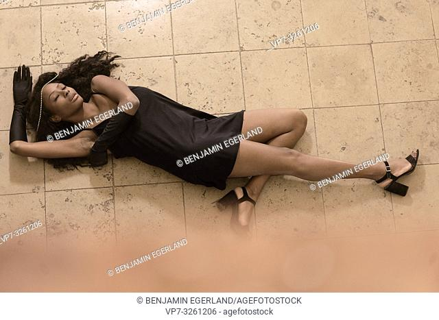 woman laying on stone floor, in Munich, Germany