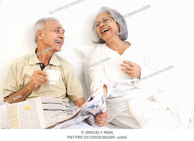 Senior couple having cup of tea with a newspaper and smiling on the bed